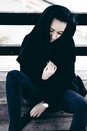 fashionable portrait of a young brunette woman in black clothes, jeans T-shirt, coat and sunglasses, in a Gothic style sad mood. on an empty beach, on an autumn cold overcast day Stock Photo