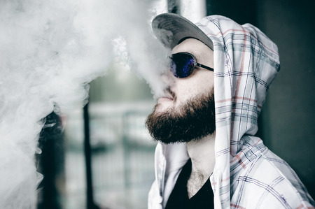 young man with beard in light checkered jacket with hood in a cap and sunglasses walking freely around city smokes an e-cigarette Stock Photo