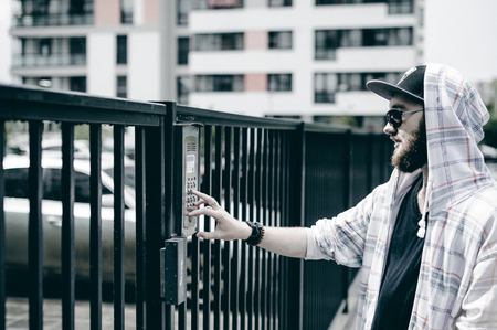 young man with beard in light checkered jacket with hood in a cap and sunglasses picks up the apartment number on the keypad to call the intercom Stock Photo