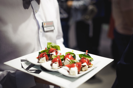 Waiter carrying trays with food. Caterring service for wedding, birthday or any company event Stockfoto