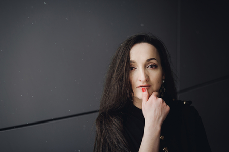 Street Portrait of a woman. fashionable brunette in black clothes on style, a walker  open air in seasons. snowfall snowflakes in frame Stok Fotoğraf