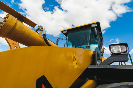 Excavator Loader Machine. Side View of Front Hoe Loader. Industrial Vehicle. Heavy Equipment Machine. Pneumatic Truck. Construction Equipment on a background of blue sky