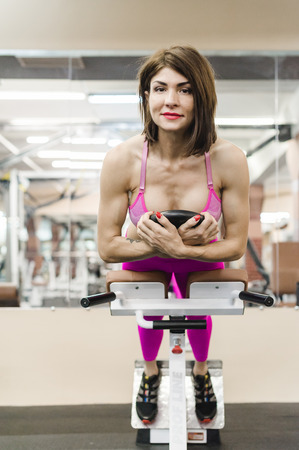 beautiful sexy woman of athletic build, engaged in workouts in gym, physical training of body. Healthy lifestyle concept. motivation and energy charge 免版税图像