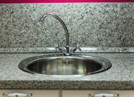silver plated: silver plated with a silver faucet in the kitchen sink Stock Photo