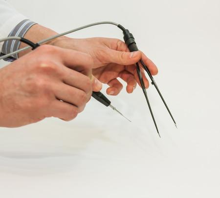 hand van de arts welke deelneming electrocautery en chirurgische pincet en verwijder de mol uit de rug van de patiënt. Radiogolven electrocoagulatie verwijderen methode
