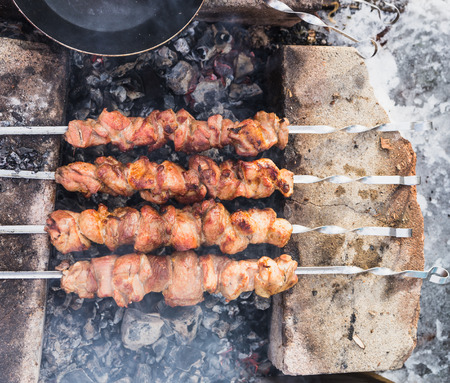 fried skewers of pork and turkey on the grill over charcoal