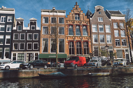 Netherlands, Holland, Amsterdam, November 3, 2015, the way through the Amsterdam channels. Architecture and boats in which people live. On photo light effect of Fuji film