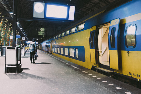 Netherlands, The Netherlands, Amsterdam, November 5, 2015 Dutch yellow double decker train is leaving a station On photo light effect of Fuji film