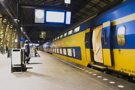 Netherlands, The Netherlands, Amsterdam, November 5, 2015 Dutch yellow double decker train is leaving a station Editorial