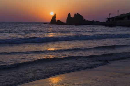 de zon gaat onder achter de berg en weerspiegelt in de zee