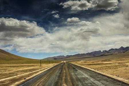 dirt background: Empty rural road going through desert under cloudy sky Stock Photo