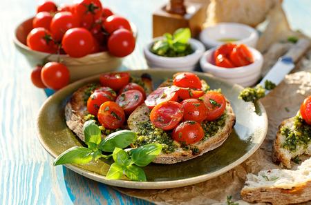 Bruschetta with cherry tomato and aromatic herb pesto Archivio Fotografico