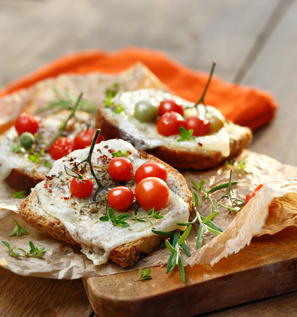 melted cheese: Bruschetta with cherry tomatoes, melted cheese and herbs Stock Photo