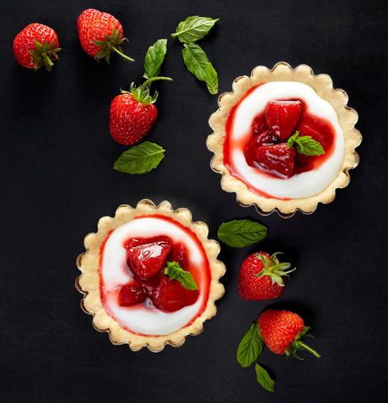 small cake: Tartlets with strawberries and vanilla cream on a black background