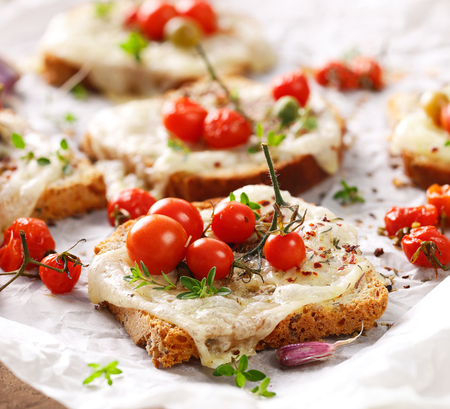 melted cheese: Bruschetta with cheese, cherry tomatoes and aromatic herbs Stock Photo