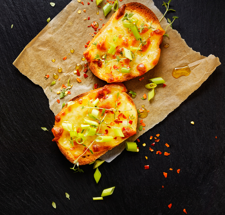 melted cheese: Small toast with cheese, scallions, chili and fresh thyme Stock Photo