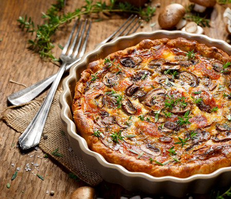 Tart with brown mushrooms on a wooden rustic table