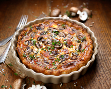 Mushroom quiche on a rustic wooden table Stockfoto