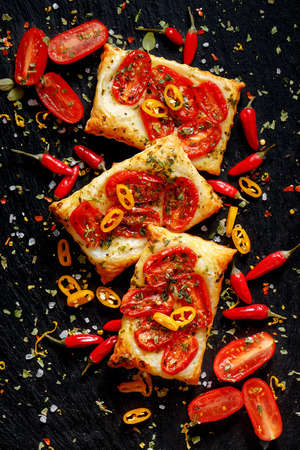 Puff pastry with tomatoes, chili peppers and herbs.