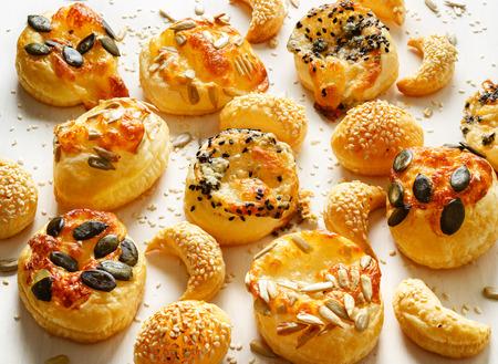 Snacks van de kaas met bladerdeeg besprenkeld met een mix van zaden op een witte achtergrond