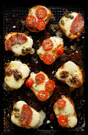 Crostini with various toppings on a dark background