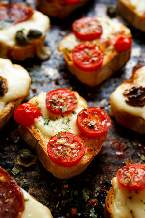 Crostini with cheese, tomatoes and herbs on a dark background Stockfoto