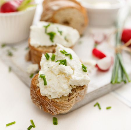 Canapes with curd cheese and fresh chive on a white table