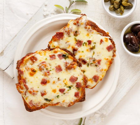 Toasted bread with cheese and chopped salami on the white board