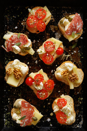 Small canapes with different toppings on a dark background