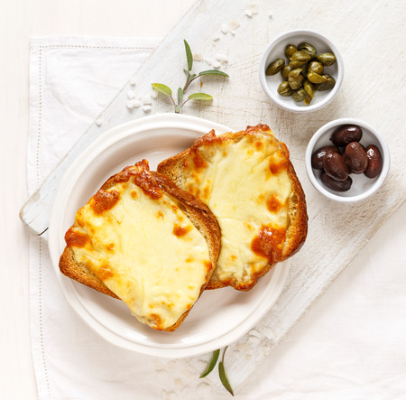 Warm Toast with melted mozzarella cheese on a white plate