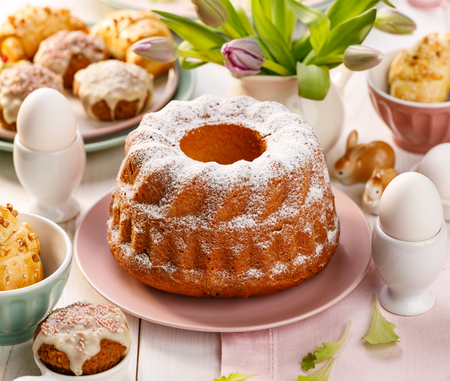 Easter yeast cake sprinkled with powdered sugar on the holiday table. Traditional polish easter dessert