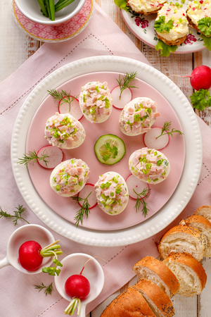 Deviled eggs, stuffed eggs filled with smoked ham, mayonnaise, egg yolks, and fresh chive on a plate, top view.Tasty breakfast, appetizer for party or holiday meals