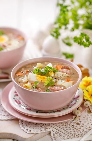 The sour soup, polish soup in a ceramic bowl. Traditional Easter dish in Poland