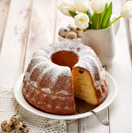 Easter yeast cake sprinkled with powdered sugar on a wooden white table. Traditional polish easter dessert