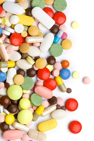 Colored pills, tablets and capsules on a white background  photo