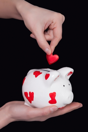 Piggy bank of a heartbreaker on a black background photo