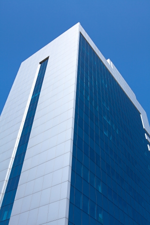 directly below: Facade of modern business building over blue sky