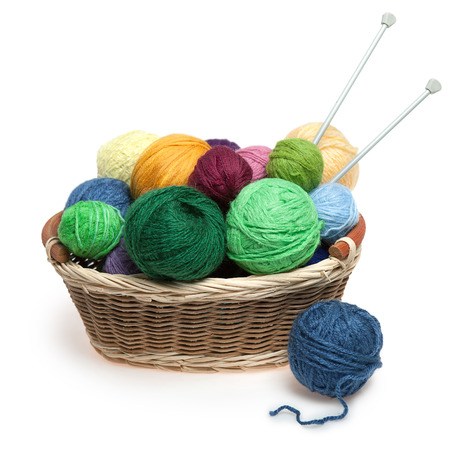 clew: Knitting yarn balls and needles in basket on a white background