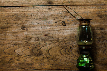 oil lamp: Oil lamp on wooden table,vintage color style, old rusty kerosene lamp .