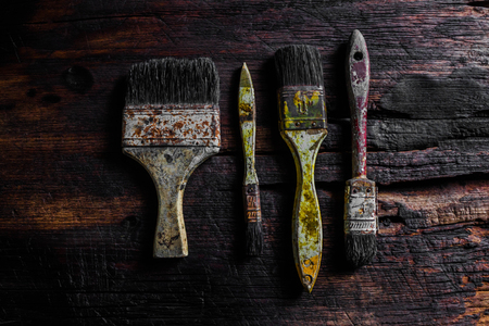 repaint: Old grungy paint brushes on the wood  .