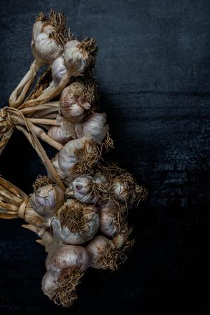 alliaceae: Purple garlic on black wood background,Close up