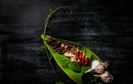 Kruiden en specerijen rond lege snijplank op donkere steen achtergrond, koken concept, Thailand. Stockfoto