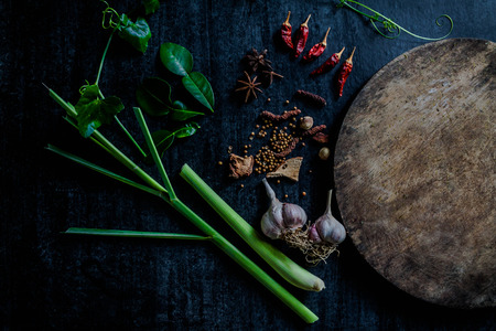 Herbs and spices around empty cutting board on dark stone background,cooking concept,Thailand. Imagens