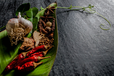 spices: Herbs and spices around empty cutting board on dark stone background,cooking concept,Thailand. Stock Photo