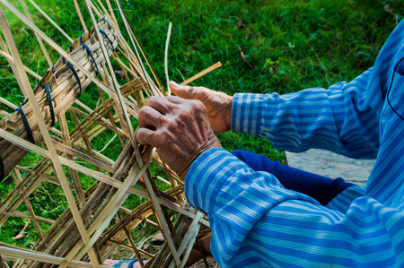 The basket-maker,Weave pattern hand bamboo, Bamboo weaving,Basket weaving , a village industry in thailand,Old Mans hands making a wicker basket