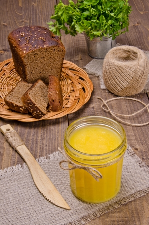 ghee: A glass jar with a thick yellow substance on a wooden surface Stock Photo