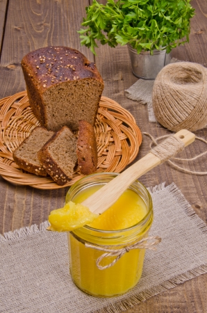 ghee: Wooden knife on a glass jar with a thick yellow substance Stock Photo