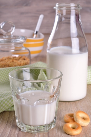 Glass and bottle of milk on a wooden surface photo