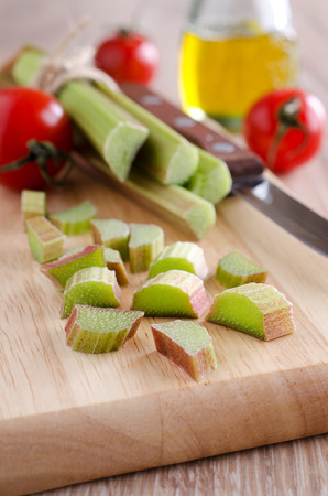 sliced ​​whole green rhubarb stalks lying on a wooden surface photo