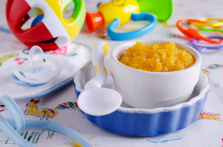 pap: Baby food orange color, resting on a background of children`s toys